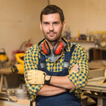 Portret męska cieśla pozycja z jego rękami krzyżować