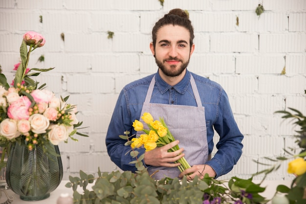 Portret męska kwiaciarnia trzyma żółtych tulipany w ręce przeciw biel ścianie