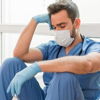Portret męska pielęgniarka jest ubranym medyczną maskę