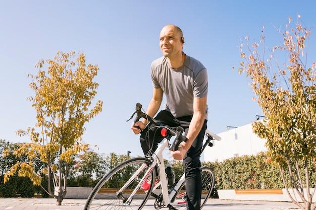 Portret męski cyklisty obsiadanie na rowerze patrzeje daleko od