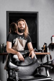 Portret męski fryzjer patrzeje kamerę