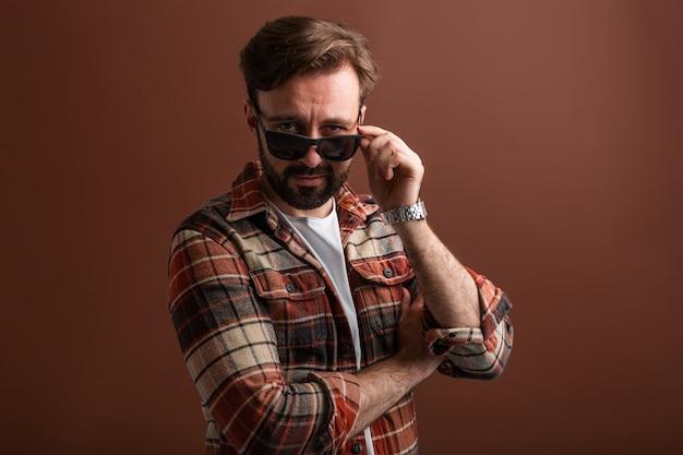 Portret męski przystojny stylowy brodaty mężczyzna na brązowym