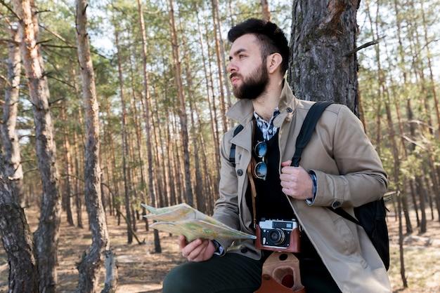 Portret męski wycieczkowicz trzyma rodzajową mapę w lesie patrzeje daleko od
