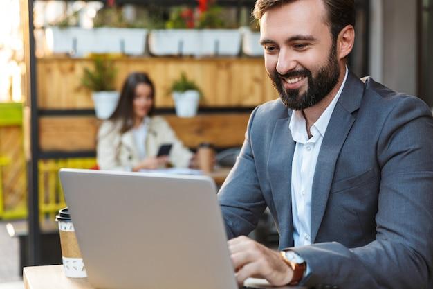 Portret męskiego biznesmena w formalnym garniturze, uśmiechając się i pracując na laptopie, siedząc w kawiarni na świeżym powietrzu