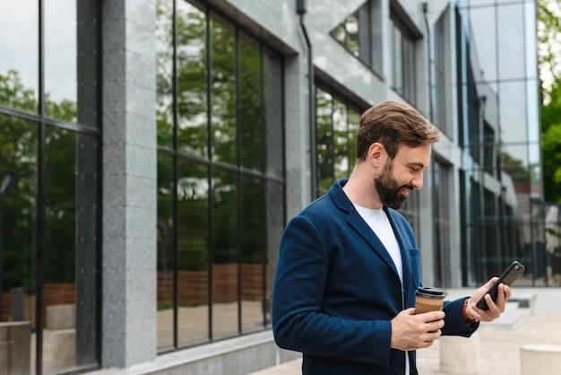 Portret męskiego biznesmena w kurtce trzymającego telefon komórkowy, stojąc na zewnątrz w pobliżu budynku z kawą na wynos