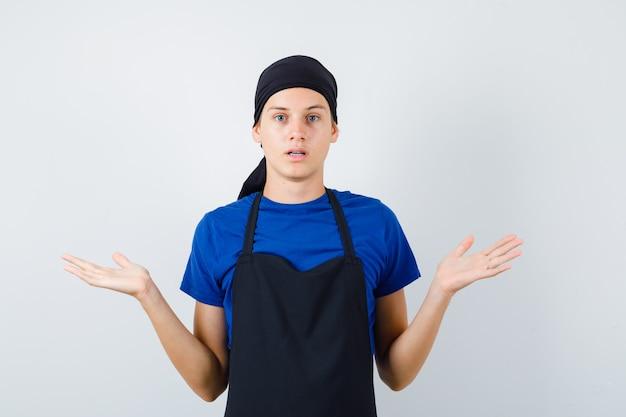 Portret męskiego kucharza nastoletniego pokazującego bezradny gest w koszulce, fartuchu i patrzący niezdecydowany widok z przodu