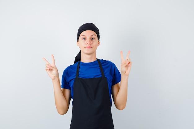 Portret męskiego kucharza nastoletniego pokazującego gest zwycięstwa w koszulce, fartuchu i wyglądającym na zadowolonego widoku z przodu