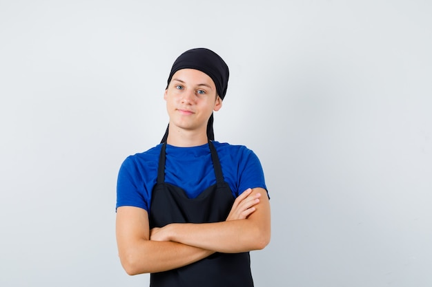Portret męskiego kucharza nastoletniego trzymającego ręce skrzyżowane w koszulce, fartuchu i patrzącego pewnie z przodu
