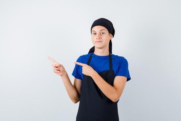 Portret męskiego kucharza nastoletniego wskazującego na lewą stronę w koszulce, fartuchu i wyglądającym pewnie z przodu