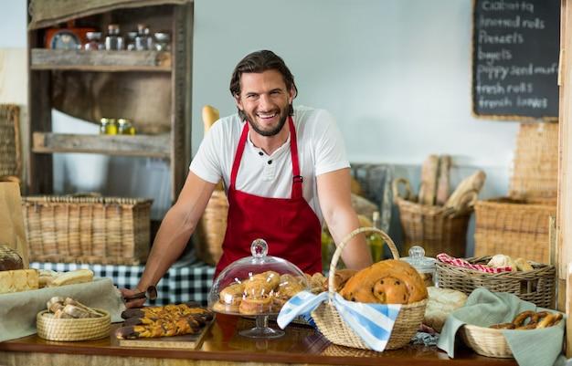 Portret męskiego personelu stojącego przy kasie w piekarni