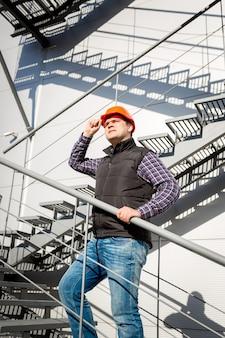 Portret męskiego pracownika w kasku stojącym na stalowych schodach