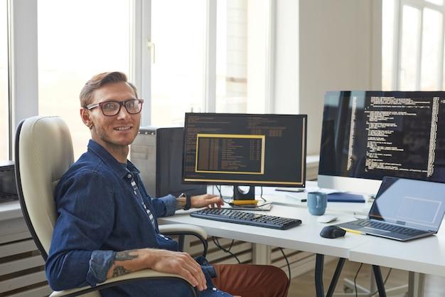 Portret męskiego programisty patrzącego na kamerę podczas pisania kodu na ekranie komputera w biurze programistów it