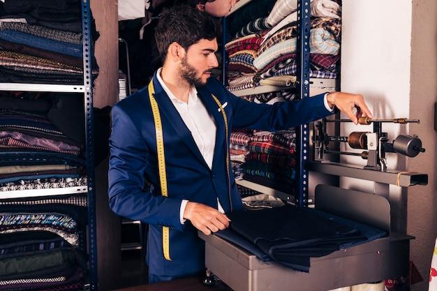 Portret męskiego projektanta mody dostosowującego maszynę do ważenia tkanin w warsztacie