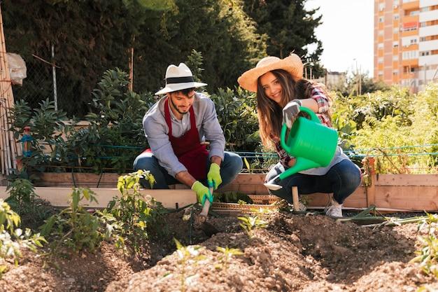 Portret męskiej i żeńskiej ogrodniczki pracuje w ogrodzie