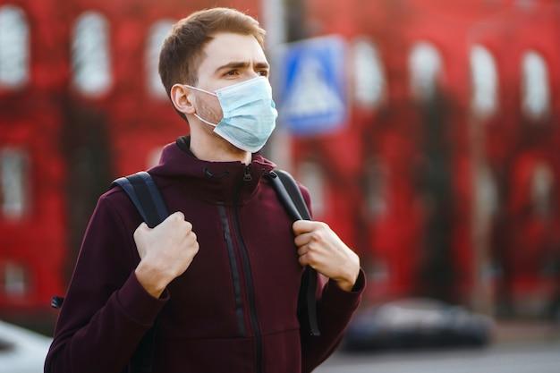 Portret mężczyzn w ochronnej sterylnej masce medycznej na jej twarzy na ulicy miasta. covid19.