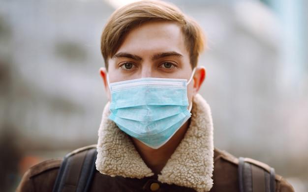 Portret mężczyzn w ochronnej sterylnej masce medycznej na jej twarzy na ulicy miasta.
