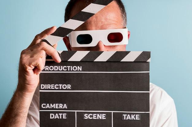 Portret mężczyzna jest ubranym 3d szkła trzyma clapperboard przed jego twarzą przeciw błękitnemu tłu