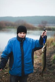 Portret mężczyzna mienia szczupaka rybia patrzeje kamera