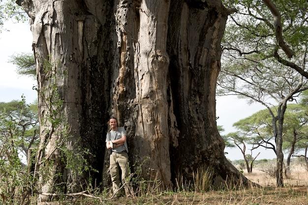Portret mężczyzna pozycja przed baobabem, tanzania, afryka