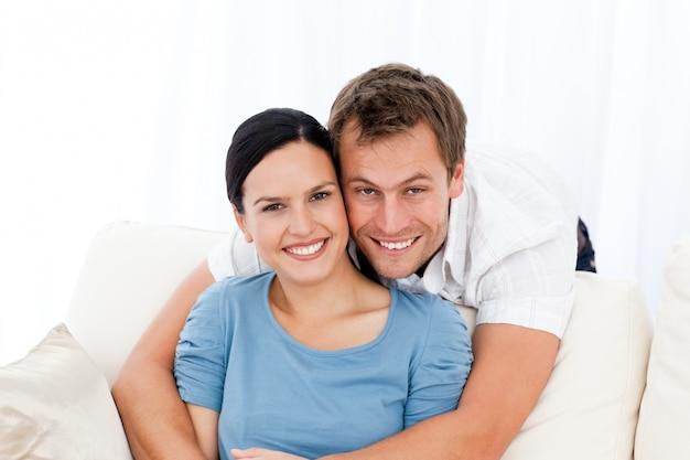 Portret mężczyzna ściska jego dziewczyny podczas gdy relaksujący na kanapie