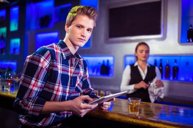 Portret mężczyzna używa cyfrową pastylkę z barmanu działaniem