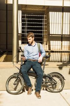 Portret mężczyzna używa telefonu komórkowego obsiadanie z bicyklem