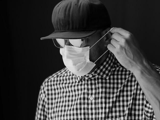 Portret mężczyzna w czapce i okularach przeciwsłonecznych, nałóż medyczną maskę na twarz. obraz czarno-biały.