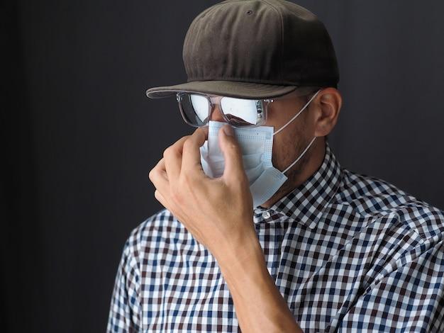 Portret mężczyzna w czapce i okularach przeciwsłonecznych, nałóż medyczną maskę na twarz.