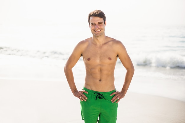 Portret mężczyzna w pływanie zwiera pozycję na plaży