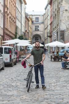 Portret mężczyzna z bicyklem przy outdoors