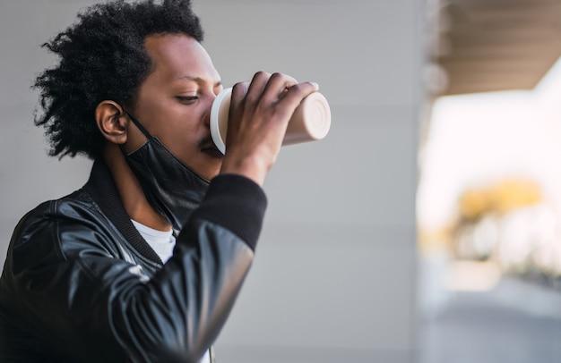 Portret mężczyzny afro picia filiżankę kawy na zewnątrz. koncepcja miejska i styl życia.