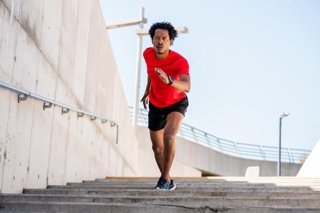 Portret mężczyzny afro sportowca działa i robi ćwiczenia na świeżym powietrzu.