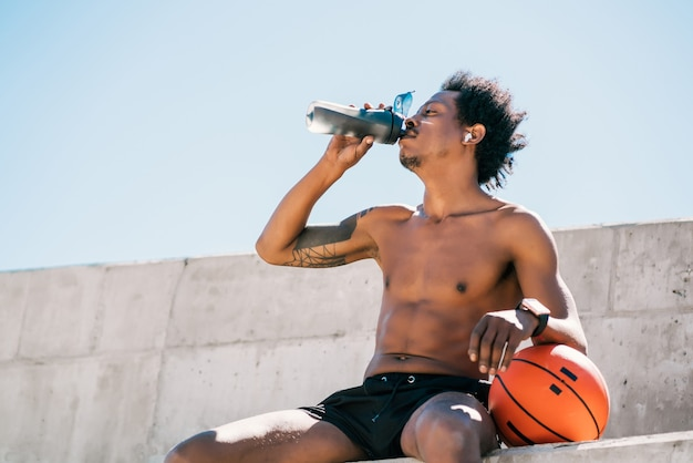 Portret mężczyzny afro sportowca wody pitnej i trzymając piłkę do koszykówki na zewnątrz. sport i zdrowy tryb życia.