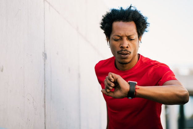 Portret mężczyzny afro sportowiec sprawdzanie czasu na jego inteligentny zegarek