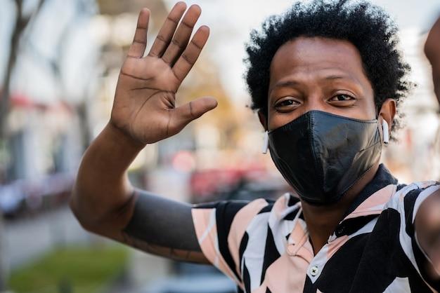 Portret mężczyzny afro turysta biorąc selfie i witając się ręką, stojąc na zewnątrz na ulicy. nowa koncepcja normalnego stylu życia.