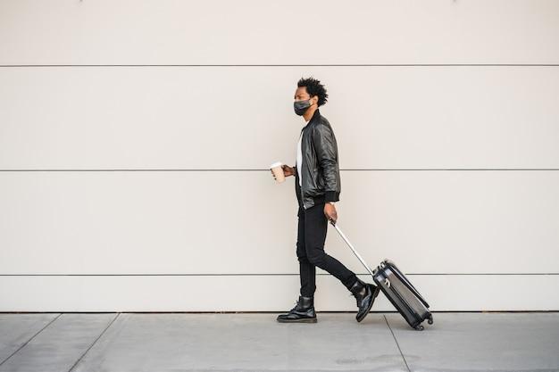 Portret mężczyzny afro turysta niosący walizkę i trzymając filiżankę kawy podczas spaceru na ulicy. koncepcja turystyki.