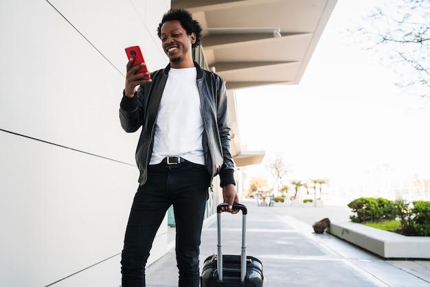 Portret mężczyzny afro turysta za pomocą swojego telefonu komórkowego i niosąc walizkę podczas spaceru na ulicy