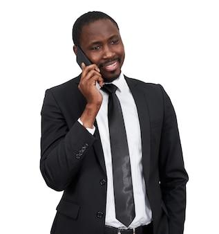 Portret mężczyzny afrykańskiego uśmiechnięty podczas rozmowy przez telefon z szarej ściany na białym tle