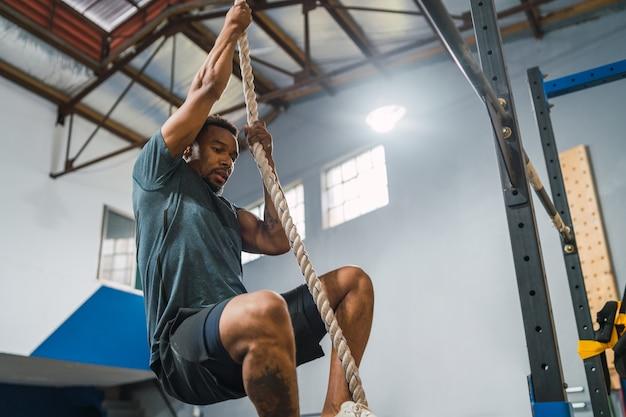 Portret mężczyzny atletycznego robi ćwiczenia wspinaczkowe na siłowni