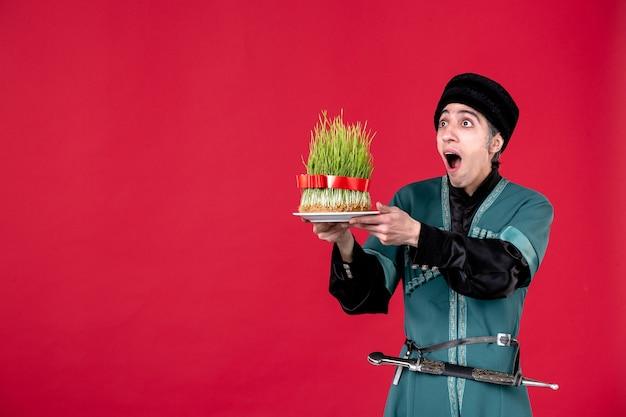 Portret mężczyzny azerskiego w tradycyjnym stroju, trzymającego zielone nasienie na czerwono
