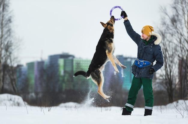 Portret mężczyzny bawiącego się z owczarkiem niemieckim w parku zimą