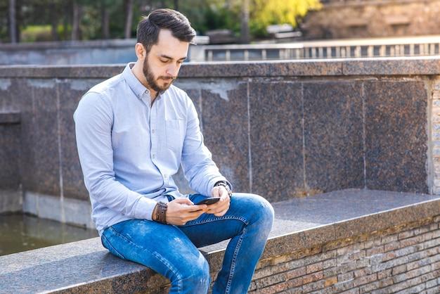 Portret mężczyzny biznesmena w koszuli z brodą, który siedzi i używa smartfona