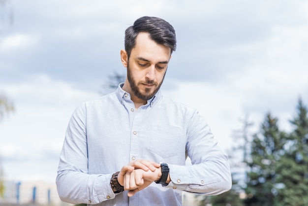 Portret mężczyzny biznesmena z brodą patrząc na zegarek na nadgarstku