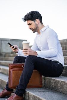 Portret mężczyzny biznesu przy użyciu swojego telefonu komórkowego, siedząc na schodach na zewnątrz