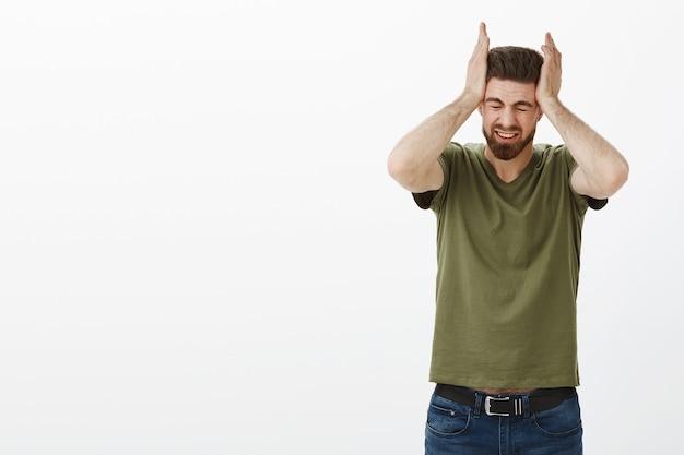 Portret mężczyzny cierpiącego na ogromny ból głowy lub migrenę chwytającego głowę obiema rękami mrużącymi oczy z bólu i niepokoju, zdenerwowanego i zestresowanego, stojącego niezadowolony nad białą ścianą