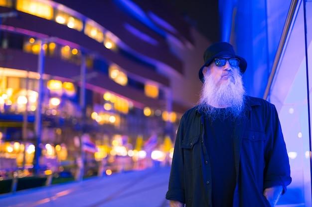 Portret mężczyzny dojrzały brodaty turysta zwiedzania ulice miasta bangkok, tajlandia w nocy