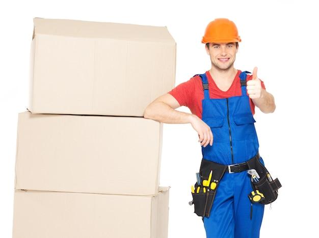 Portret mężczyzny dostawy pracownika z pudełkami papieru pokazujący kciuk do góry znak na białym tle