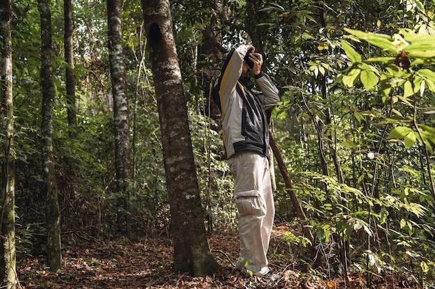Portret mężczyzny fotografującego aparatem na łonie natury.