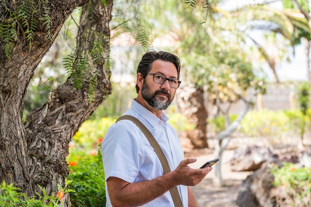Portret mężczyzny freelancera korzystającego z telefonu komórkowego na świeżym powietrzu w parku z roamingowym połączeniem internetowym