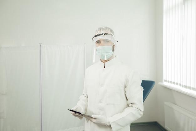 Portret mężczyzny ginekologa w kombinezonie ochronnym przygotowuje się do przyjęcia pacjentów podczas kwarantanny koronawirusa. lekarz w środkach ochrony indywidualnej podczas pandemii.